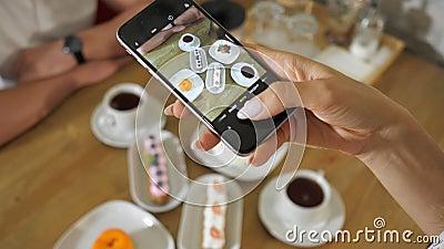 Une femme prend des photos de gâteaux savoureux et de thé sur une table en bois banque de vidéos