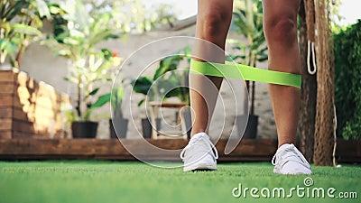 Une femme proche fait de l'exercice avec une bande résistante sur la pelouse banque de vidéos