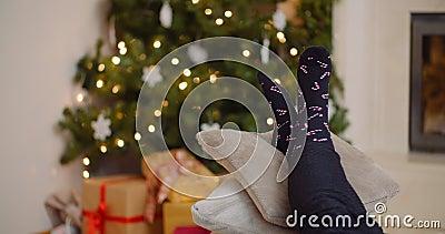 Une femme se reposant les jambes sur des coussins contre le sapin de Noël banque de vidéos