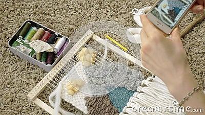 Une femme tisse sur un métier à tisser qu'une belle broderie a fait du fil, dans un studio à la maison, des photographies au télé banque de vidéos