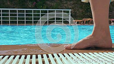 Une fille aux pieds nus se promène au bord d'un bassin d'eau bleue claire banque de vidéos