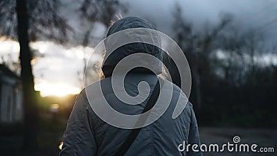 Une fille dans une veste à capuchon avance contre le coucher du soleil Lecture lente banque de vidéos