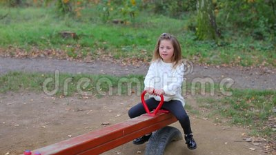 Une fille en vêtements blancs monte dans une balançoire d'équilibre dans un parc de la ville banque de vidéos