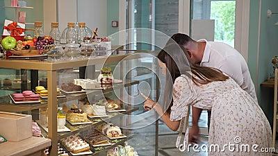 Une fille et un mec regardent de savoureux gâteaux dans une vitrine de boutique banque de vidéos