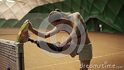 Une fille handicapée mince étire sa jambe blessée sur le filet de tennis avant le jeu prothèse indoors banque de vidéos