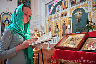 Une fille lit une prière dans l église.
