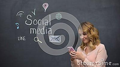 Une fille publie un message sur les médias sociaux en utilisant son téléphone portable, une connexion mondiale sur Internet banque de vidéos