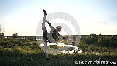 Une fille stretchy se tournant vers l'avant et faisant un front scindé comme une voile venteuse au coucher du soleil au ralenti banque de vidéos