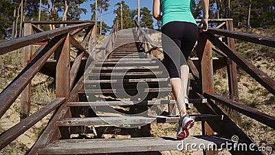 Une fillette grimpe les escaliers en bois de la jetée Athlète de course en escalier clips vidéos