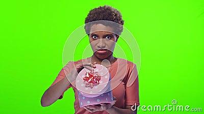 Une jeune femme à la peau sombre ouvre une boîte avec joie et déçue banque de vidéos