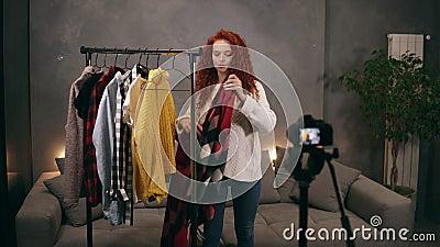 Une jeune femme à tête rouge élégante a enregistré une vidéo pour un blog en ligne sur les vêtements à la mode debout à côté du r clips vidéos