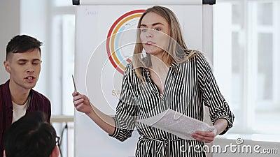Une jeune femme d'affaires professionnelle et heureuse dirige la discussion d'équipe dans un bureau moderne et branché, expliqua clips vidéos