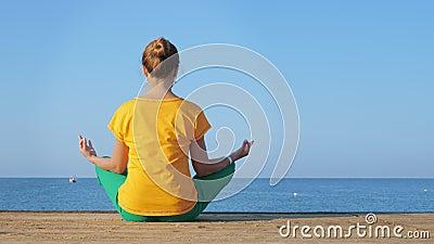 Une jeune femme en vêtements colorés pratique le yoga à la mer ou à l'océan banque de vidéos