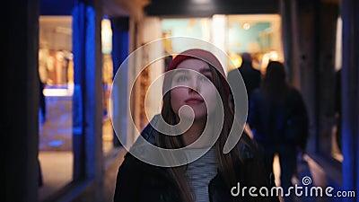 Une jeune femme marchant sur la rue et regardant les fen?tres de magasin dans l'?clairage au n?on clips vidéos