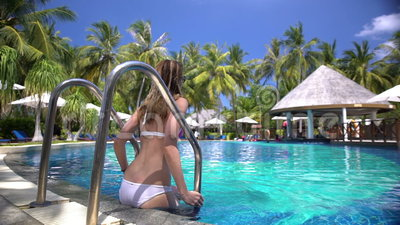 Une jeune femme mince appréciant la natation dans la piscine sur une station de vacances tropicale clips vidéos