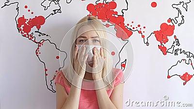 Une jeune femme porte un masque médical sur une carte du monde banque de vidéos