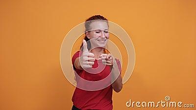 Une jeune femme souriante en chemise rouge pointant directement, souriant au-dessus d'un mur orange banque de vidéos