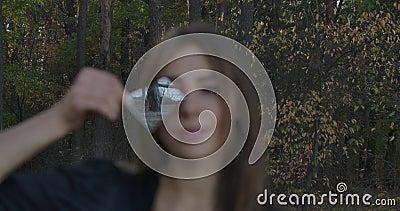 Une jeune fille caucasienne tenant un fragment de miroir cassé devant son visage Forêt d'automne et reflet du lac dans banque de vidéos