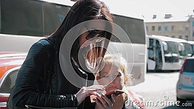 Une jeune maman et sa fille achètent un billet de bus en ligne, le concept de réservation en ligne banque de vidéos