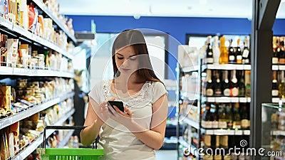 Une jolie femme utilise le téléphone avec un panier dans un supermarché, envoie des SMS banque de vidéos