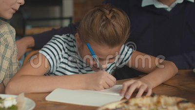 Une jolie fille écrit quelque chose au déjeuner, les parents s'assoient avec elle et aident clips vidéos