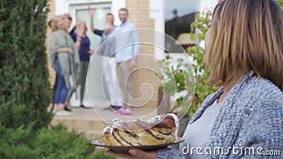 Une joyeuse femme caucasienne avec un gâteau souriant et regardant la caméra debout au premier plan tandis que la compagnie de ge banque de vidéos