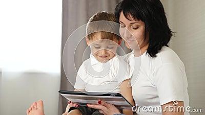 Une mère et son petit fils utilisent un Tablet PC pour regarder un film, jouer à un jeu ou appeler clips vidéos
