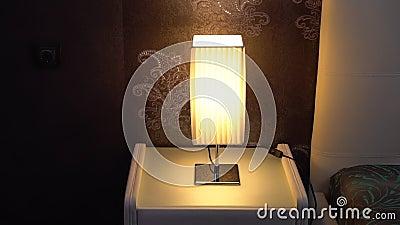 Une main du ` s d'homme allume la lumière de table sur une table de chevet banque de vidéos