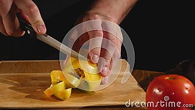 Une main du ` s de cuisinier coupe un paprika par un couteau sur une planche à découper banque de vidéos