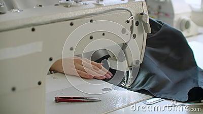 Une main femelle pousse le matériau à travers une machine à coudre banque de vidéos