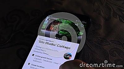 Une personne employant l'appli d'Airbnb sur un smartphone - destinations les explorant de voyage banque de vidéos