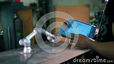 Une personne utilise le comprimé pour commander un bras robotique fonctionnant banque de vidéos