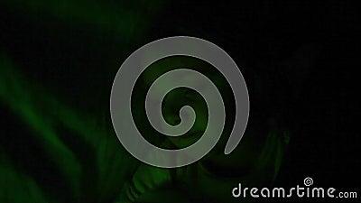 Une petite fille joue sous les couvertures avec une lampe multicolore banque de vidéos