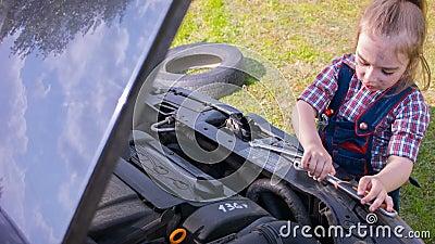 Une petite fille répare un moteur de voiture avec une grosse clé clips vidéos