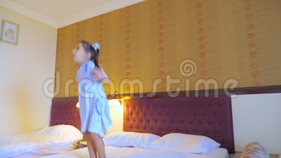 Une petite fille saute sur le lit dans une chambre d'hôtel, s'amuse et aime la vie clips vidéos