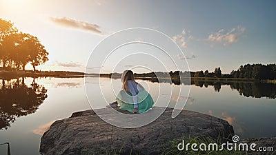 Une petite fille solitaire se trouve sur le rivage d'un lac et fait éclater de l'eau au coucher du soleil Vidéo en mouvement banque de vidéos