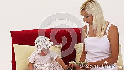 Une petite fille tire l'argent hors de sa bourse banque de vidéos