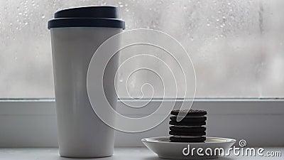 Une tasse avec un couvercle avec des stands de café sur le rebord de la fenêtre, à côté d'une assiette, sont des biscuits empilés banque de vidéos