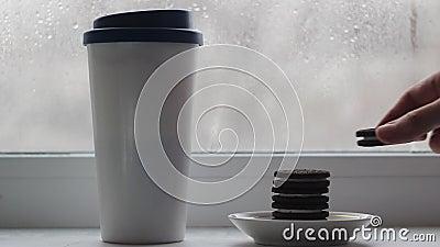Une tasse avec un couvercle avec des stands de café sur le rebord de la fenêtre, à côté d'une assiette, sont des biscuits empilés clips vidéos