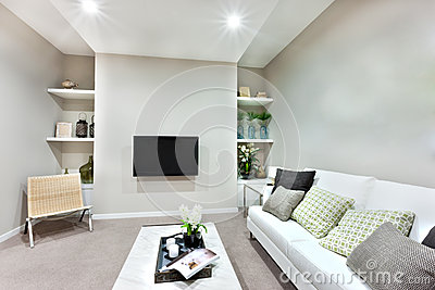 la vue troite du salon moderne avec les oreillers blancs sur le sofa blanc et une petite table sur la moquette l est galement chaise en bois galement - Un Salon De Luxe