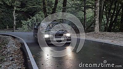 Une voiture japonaise noire commence à dériver avec du skidling et de la fumée sur la route de campagne banque de vidéos