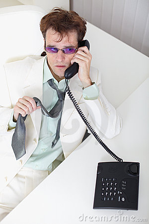 Uneasy young businessman speaks on phone