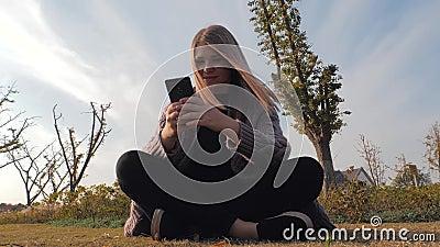 Ung attraktiv blond flicka som sitter utomhus i parken med telefon stock video