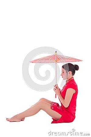 Ung attraktiv sammanträdekvinna i röd japansk klänning med umbrel