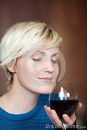 Ung blond kvinna med rött vinexponeringsglas