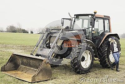 Ung kvinna bredvid en traktor
