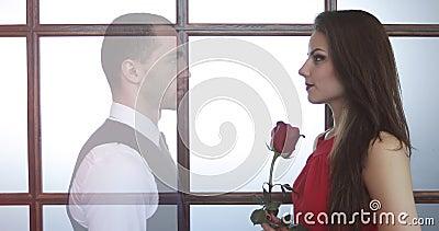 Ung kvinna i en röd klänning med blommor i hennes händer stock video
