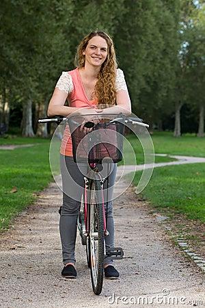 Ung kvinna med en cykel
