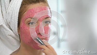 Ung kvinna med en pålagd vit handduk hennes framsida en rosa fuktamaskering stock video