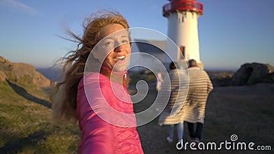 Ung kvinna med hennes stora familj som leder hennes make som går in mot den steniga nordliga stranden stock video